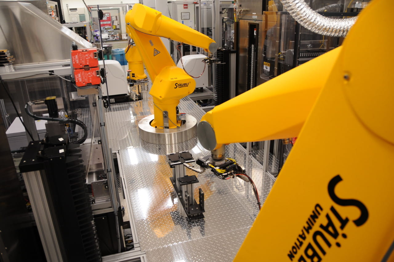 Robots handle assays in a HTS system