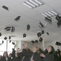 graduating students throwing their hats up